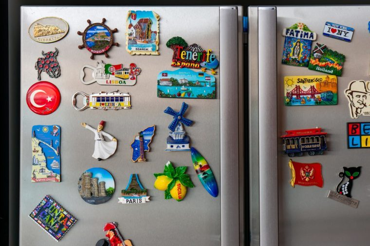 Lowicz, Poland - July 22, 2018: Mix of magnet from different countries and cities attached on a fridge. Those souvenirs are collected by many tourists after spending vacation.