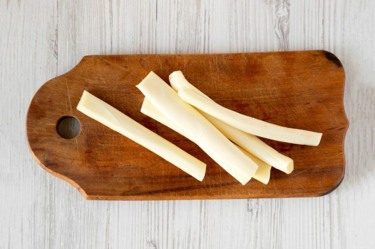 Top view, string cheese on rustic wooden board over white wooden background, top view. Healthy snack. Copy space.