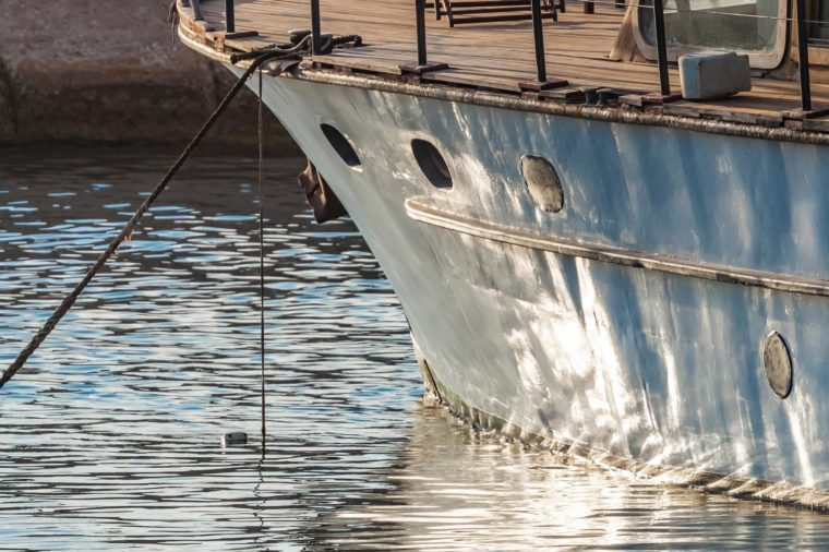 Closeup of bow of old wooden boat anchored
