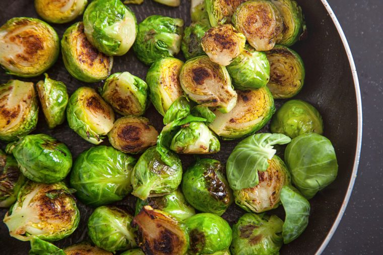 Fresh fried brussel sprouts in a black frying pan