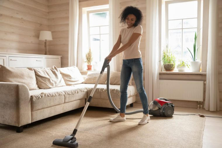 Full length positive 30s mixed race woman enjoy weekend time at modern cozy apartments, girl using vacuum cleaning carpet in living room at sunny warm day, Housekeeping chores and home routine concept