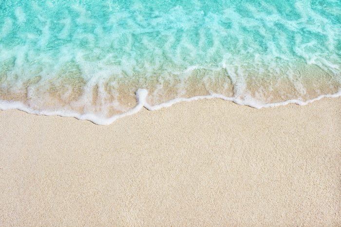 Soft beautiful ocean wave on sandy beach. Background.