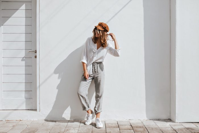 Stylish girl in gray pants and white cotton blouse posing near white wall. Photo of woman in cap and glasses