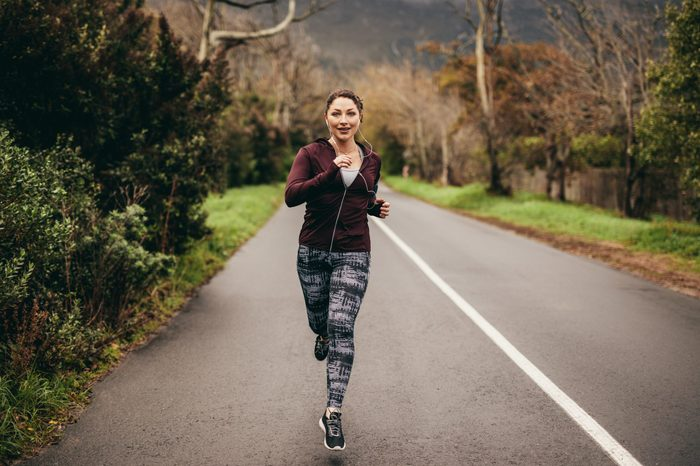 Portrait of fit young woman running on road in morning. Female jogging outdoors in morning.