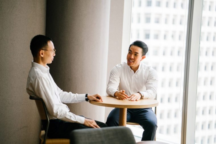 Two Chinese Asian business men have a chat at a table in the office in a meeting room during the day. They are professionally dressed in shirt and pants and having a focused discussion together.