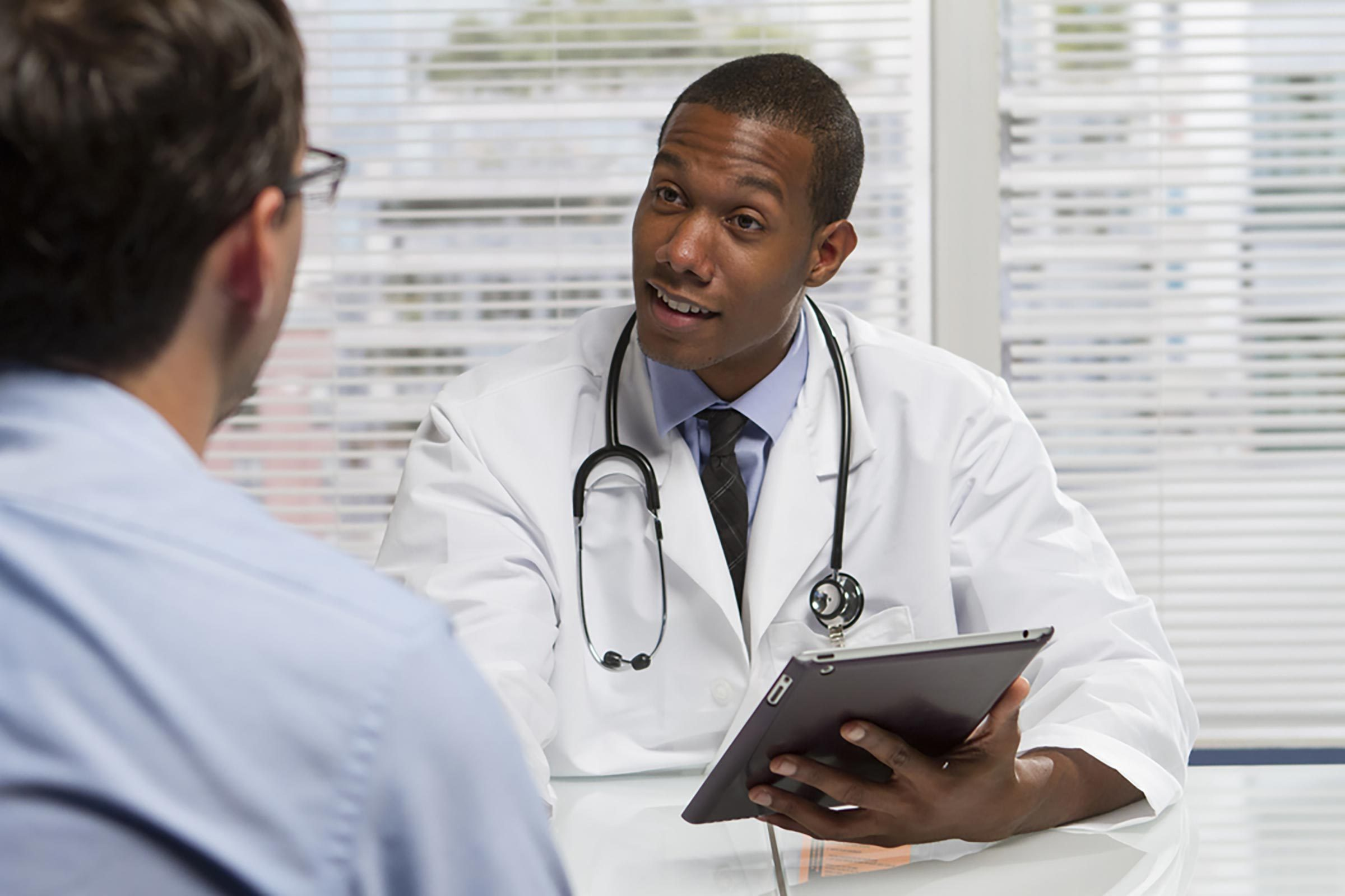 African-American doctor with a stethoscope and clipboard shaking hands with a patient