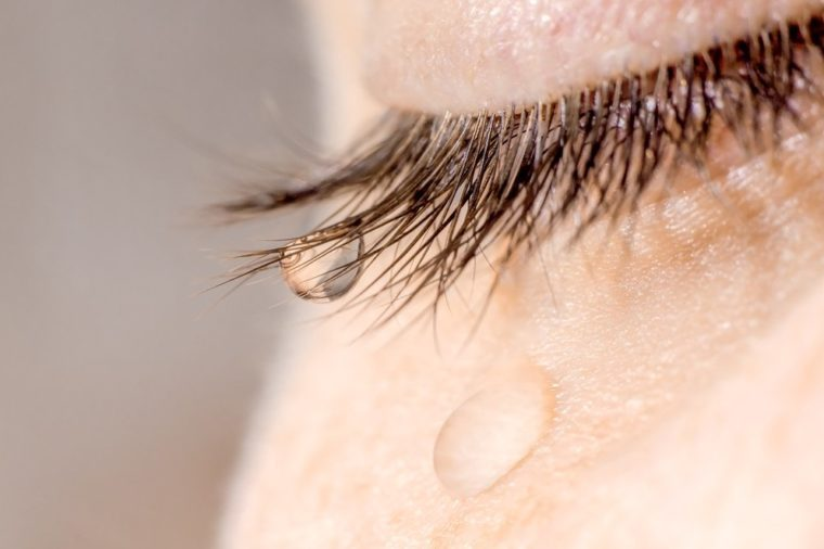 A tear on eyelashes and cheek.