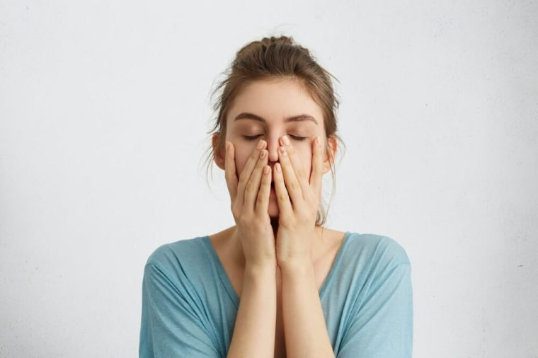 Stressed or tired woman with hands on her face