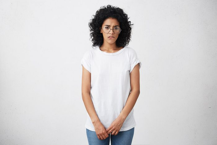 Woman wearing glasses biting her lip and looking worried