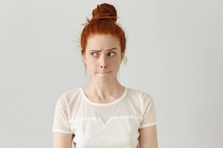 Anxious or stressed woman looking away with lips pursed