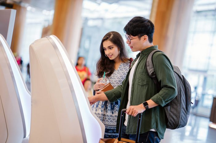 A portrait of a pair of young and excited Asian travelers (Korean man and his Indian friend) checking in to board their plane for their holiday at an automated check-in booth in the airport.