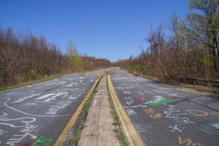 Abandoned road of Centralia covered with chalk graffiti in a bright sunny spring day.