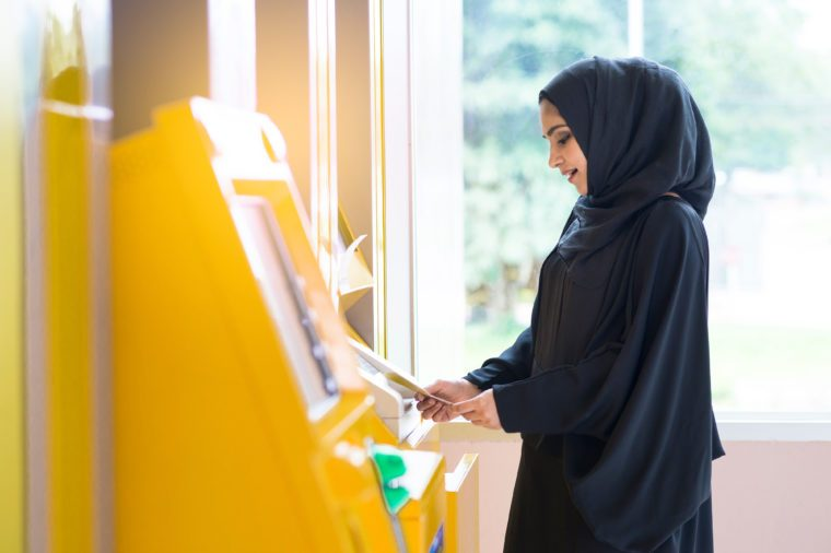 Arab woman and automated teller machine . Woman withdrawing money or checking account balance.