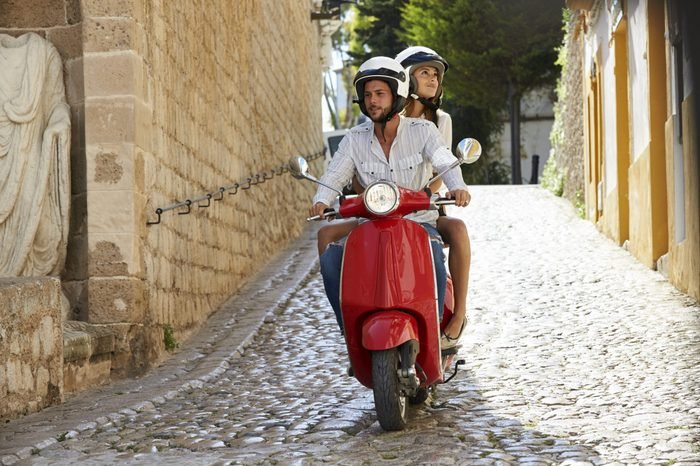 Couple riding motor scooter in old Ibiza street, full length