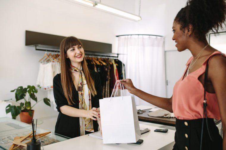 Customer shopping designer wear at a fashion boutique. Woman entrepreneur handing over shopping bag to the customer.