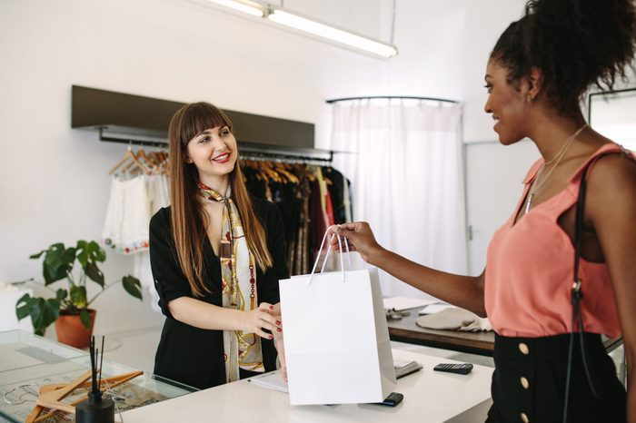 Customer shopping designer wear at a fashion boutique. Woman entrepreneur handing over shopping bag to the customer.