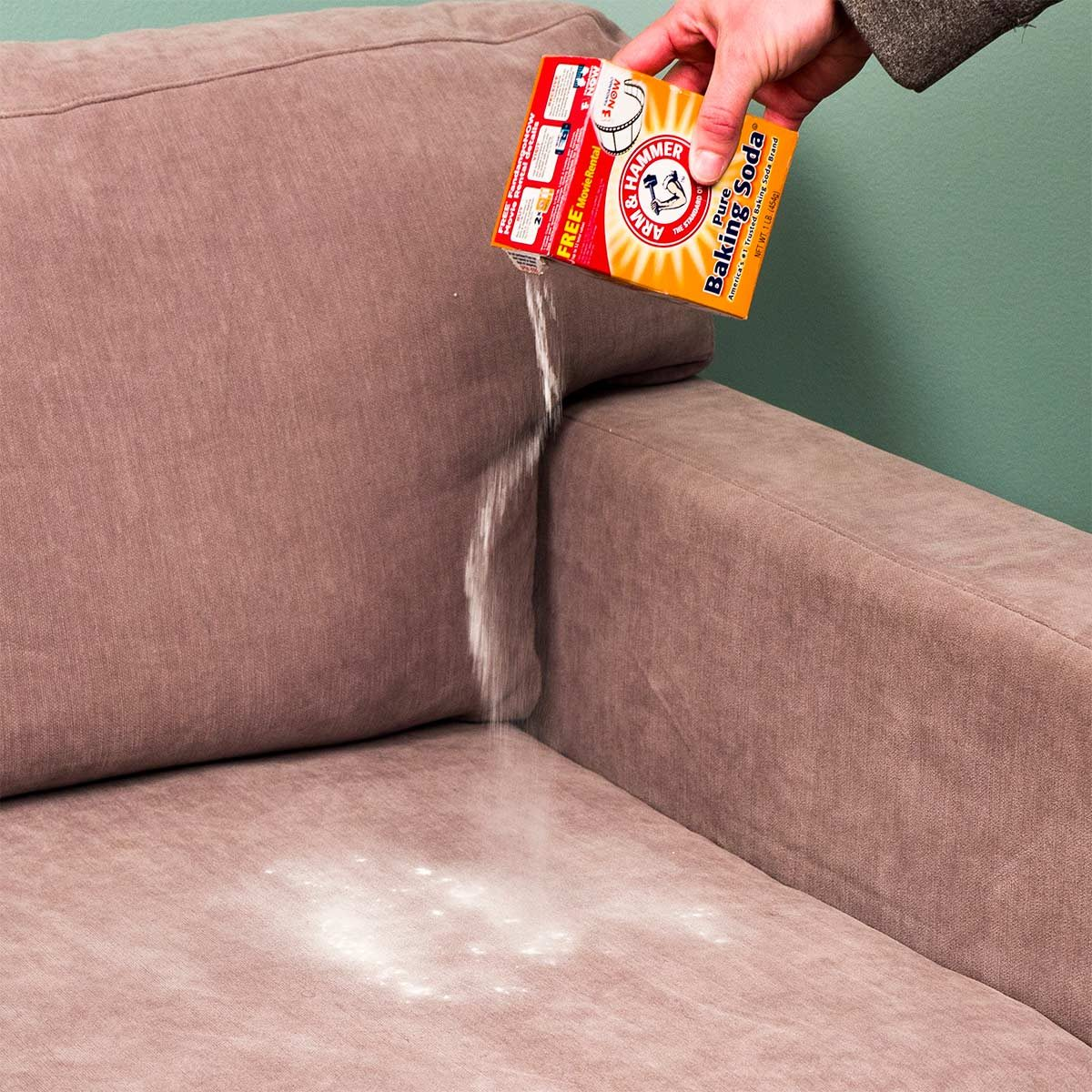 pouring baking soda onto upholstery