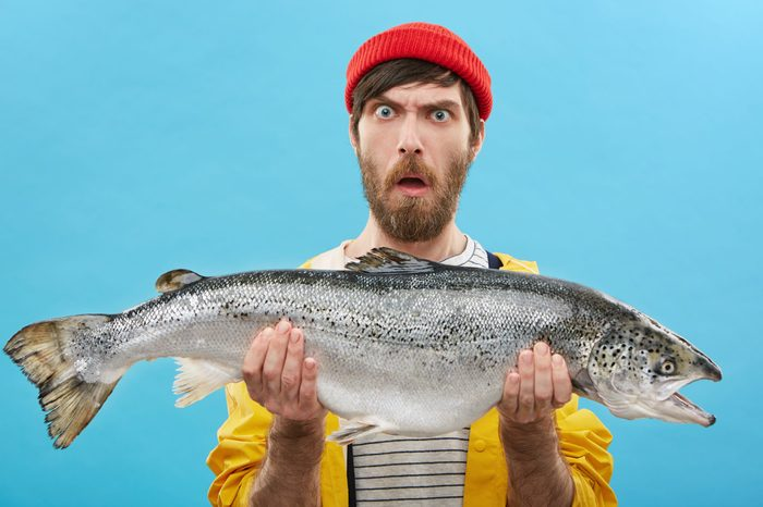 Headshot of funny emotional young bearded Caucasian fisherman in hat and raincoat holding large salmon in both hands, staring at camera with shocked look, can't believe that he caught such a big fish