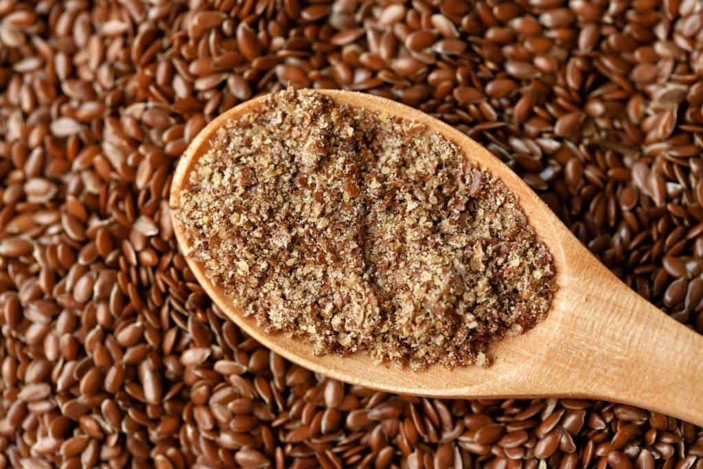 spoonful of ground flaxseed and whole flaxseeds