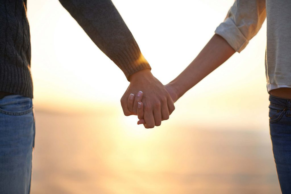 man and woman holding hands at sunset