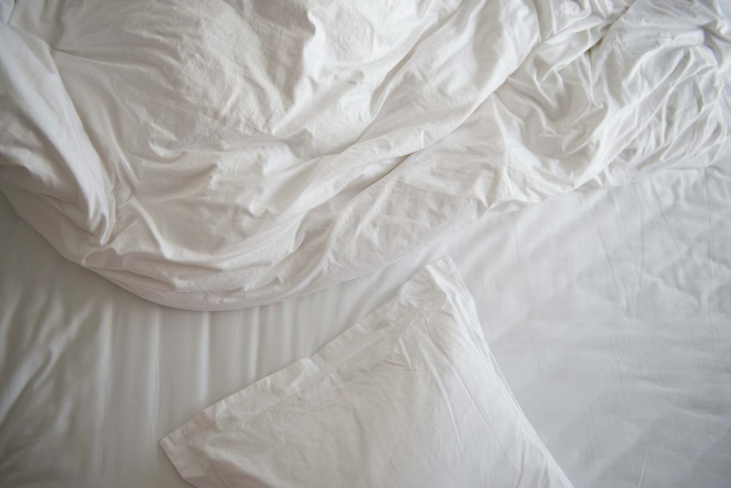 unmade bed with white pillow, blanket, and comforter