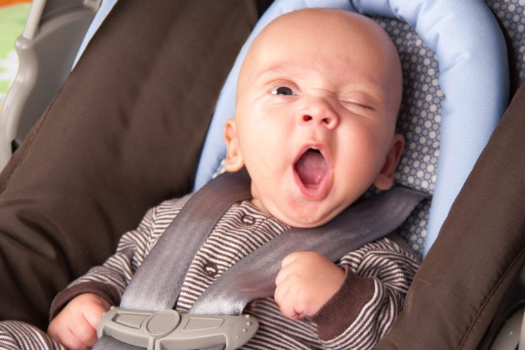 Portrait of a yawning baby Boy In Safety Seat