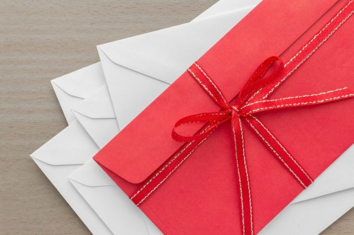 pile of envelopes with red envelope on top