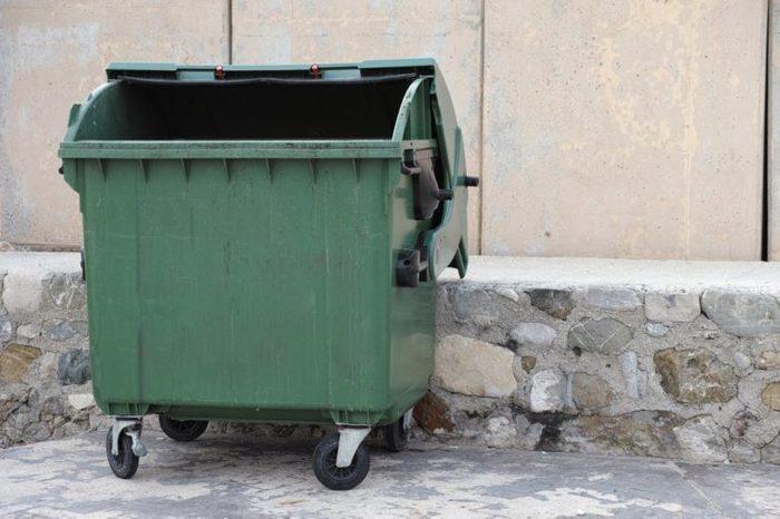 Green empty trash dumpster. Close up.