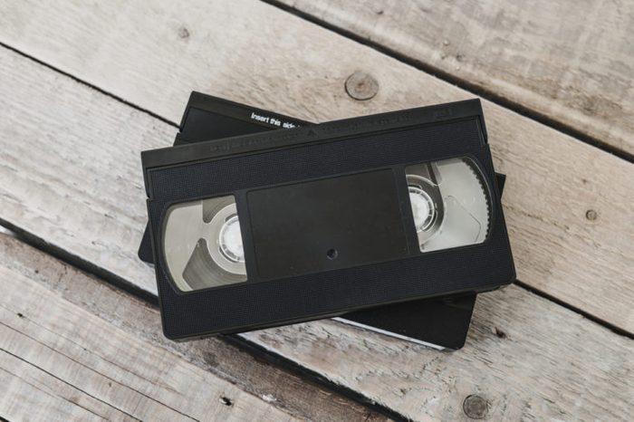 stack of VHS video tape cassette on white wooden table, retro filter