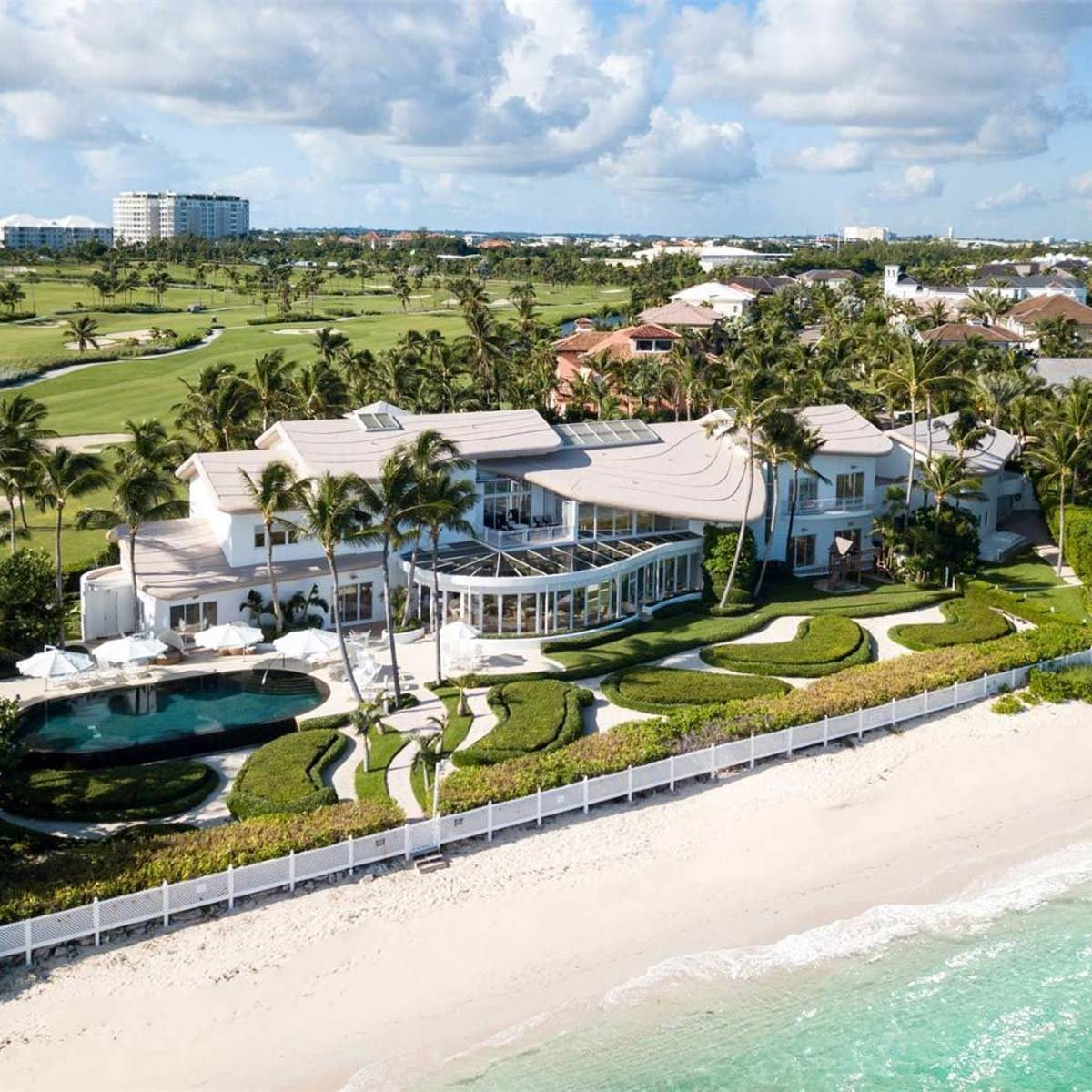 mansion on the ocean with a golf course behind
