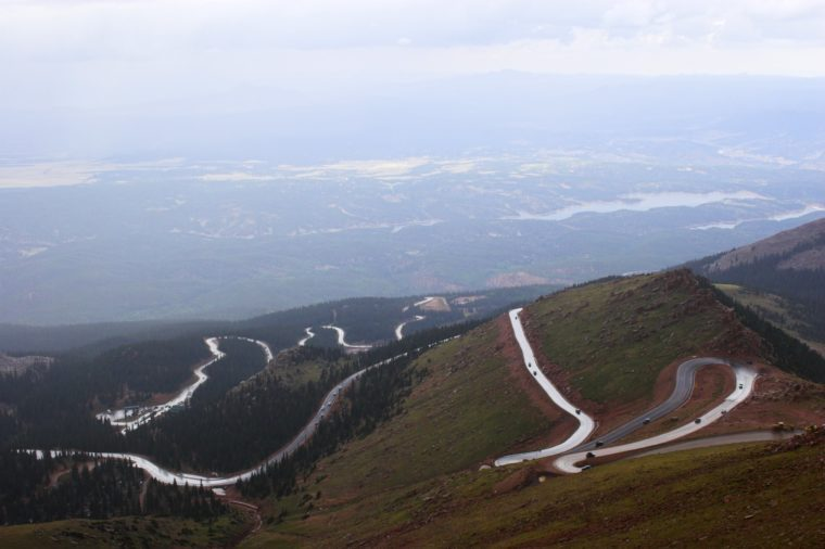 Winding road to Pike's Peak in Colorado surrounded by colorful mountain prairies during drizzle rain