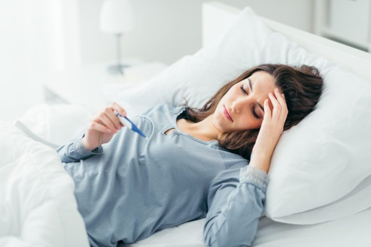 Woman with flu virus lying in bed, she is measuring her temperature with a thermometer and touching her forehead