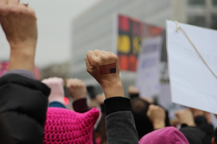 Woman's fist with US flag raised in the air at Women's March in Washington DC