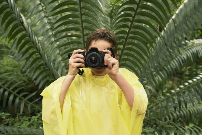 Young boy in raincoat taking photos in forest during field trip