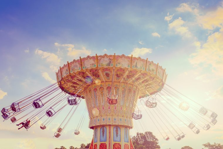 Wave Swinger ride against blue sky, vintage filter effects - a swinging carousel fair ride in amusement park at dusk