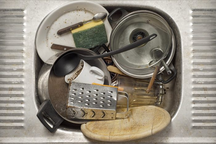Dirty dishes, utensils in the metal sink background