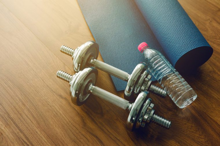 Pair of dumbbells, blue yoga mat, and bottle of water