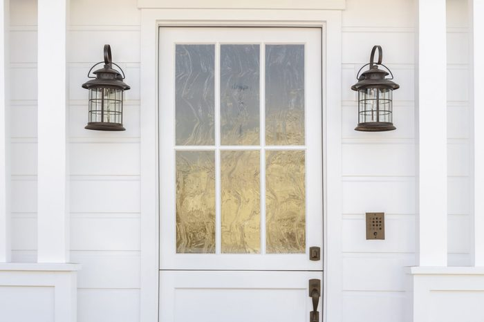 Cropped horizontal shot of a white door to a classic, white, family home in daytime. The door has intricate, etched, glass detail. Also see is light fixtures, columns, and a door bell.