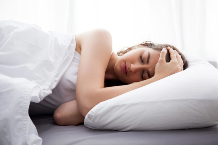 woman sleeping on her side in bed, holding her head