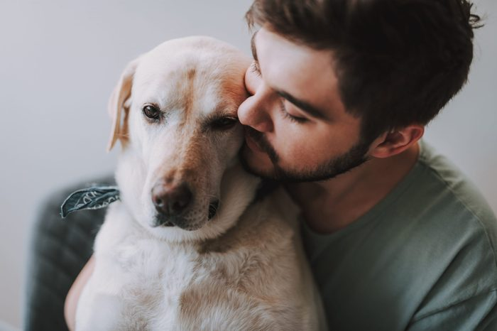 Close up of a bearded man kissing his dog while enjoying rest together