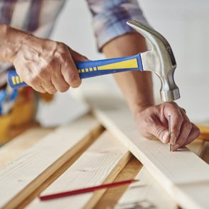 $1 solutions - Carpenter with hammer hitting nails
