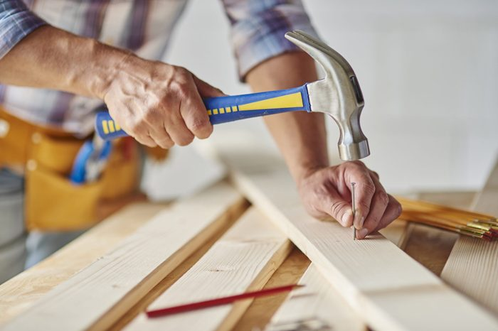 Carpenter with hammer hitting nails