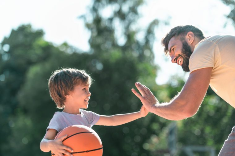 Happy boy and dad with a ball on the basketball court