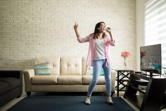 Independent woman singing karaoke alone in her apartment and having fun in the living room