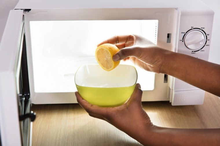 Human Hand Putting Sliced Lemon In Bowl Near Open Microwave