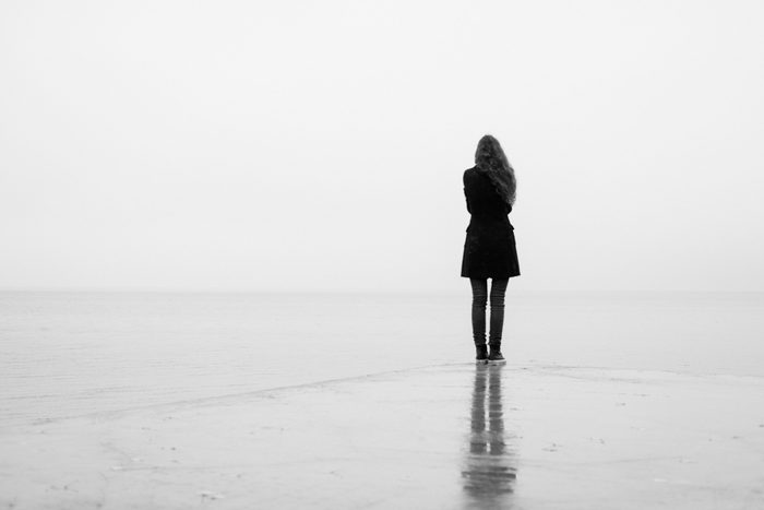 A lonely girl looks out into the distance in the rain. Black and white. Loneliness
