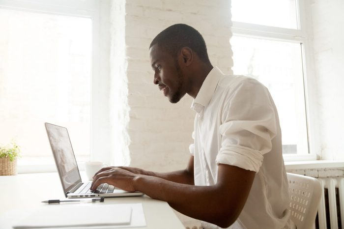 African businessman working on laptop sitting at home office desk, happy black intern employee looking at computer screen typing or browsing web, using software application for business and education