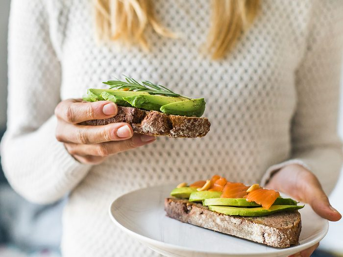 Natural remedies for high blood pressure - close up of woman holding plate with avocado toast as fresh snack, day light.