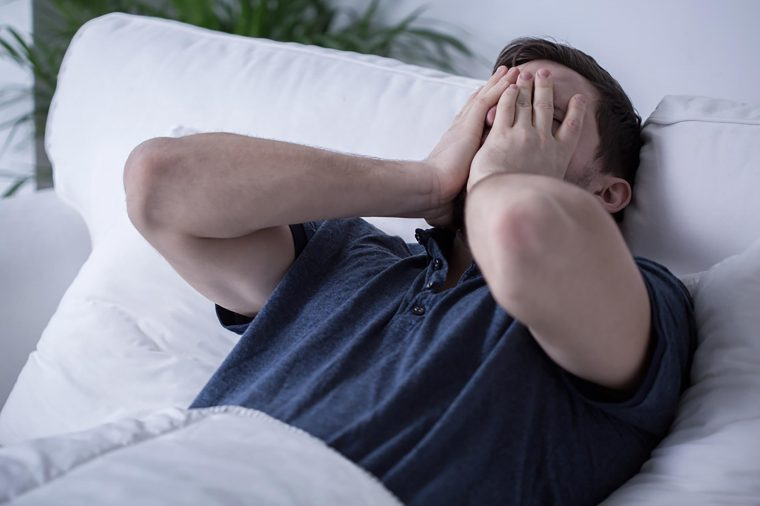 Man in bed with hands over face