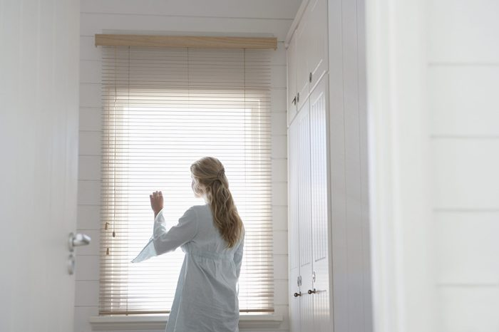 Rear view of young woman looking through window blinds at home
